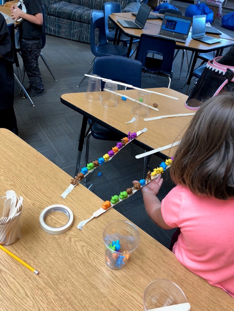 Young girl creating bridge with plastic elephants on it.