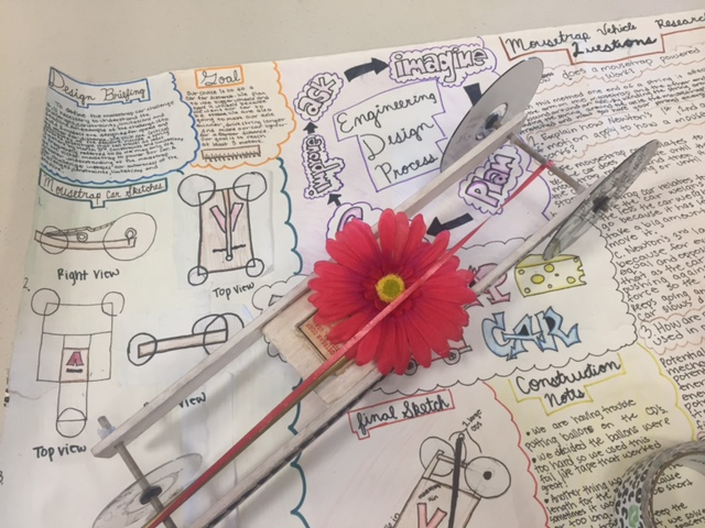 A mouse trap car with a pink flower and a very detailed sketch in background.
