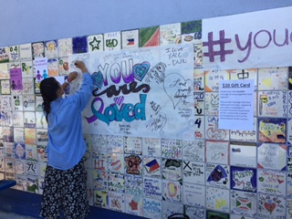 Student writing on  You Are Loved  banner